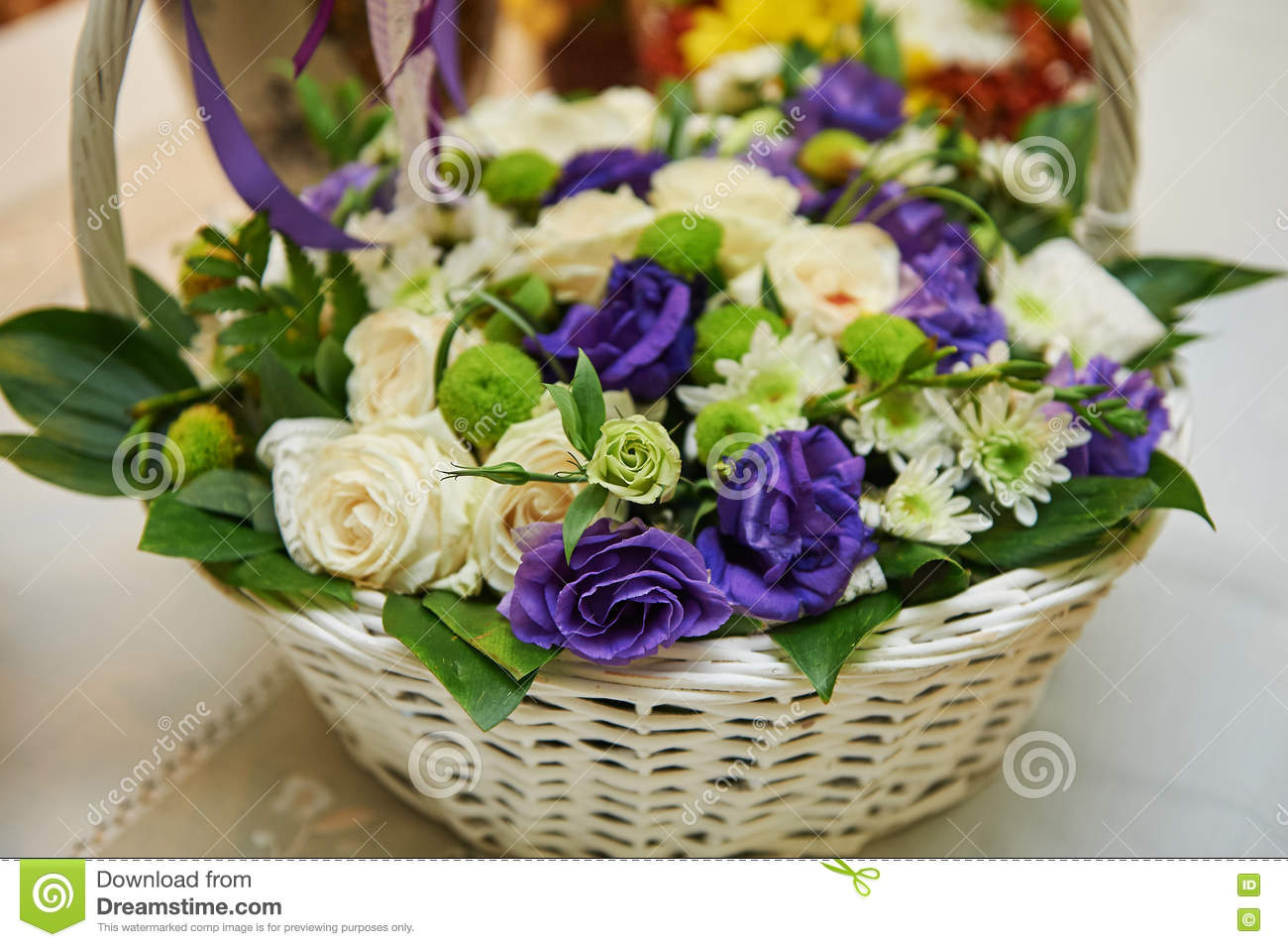 Beautiful bouquet of white and purple flowers in basket on wooden royalty free stock photo izmirmasajfo