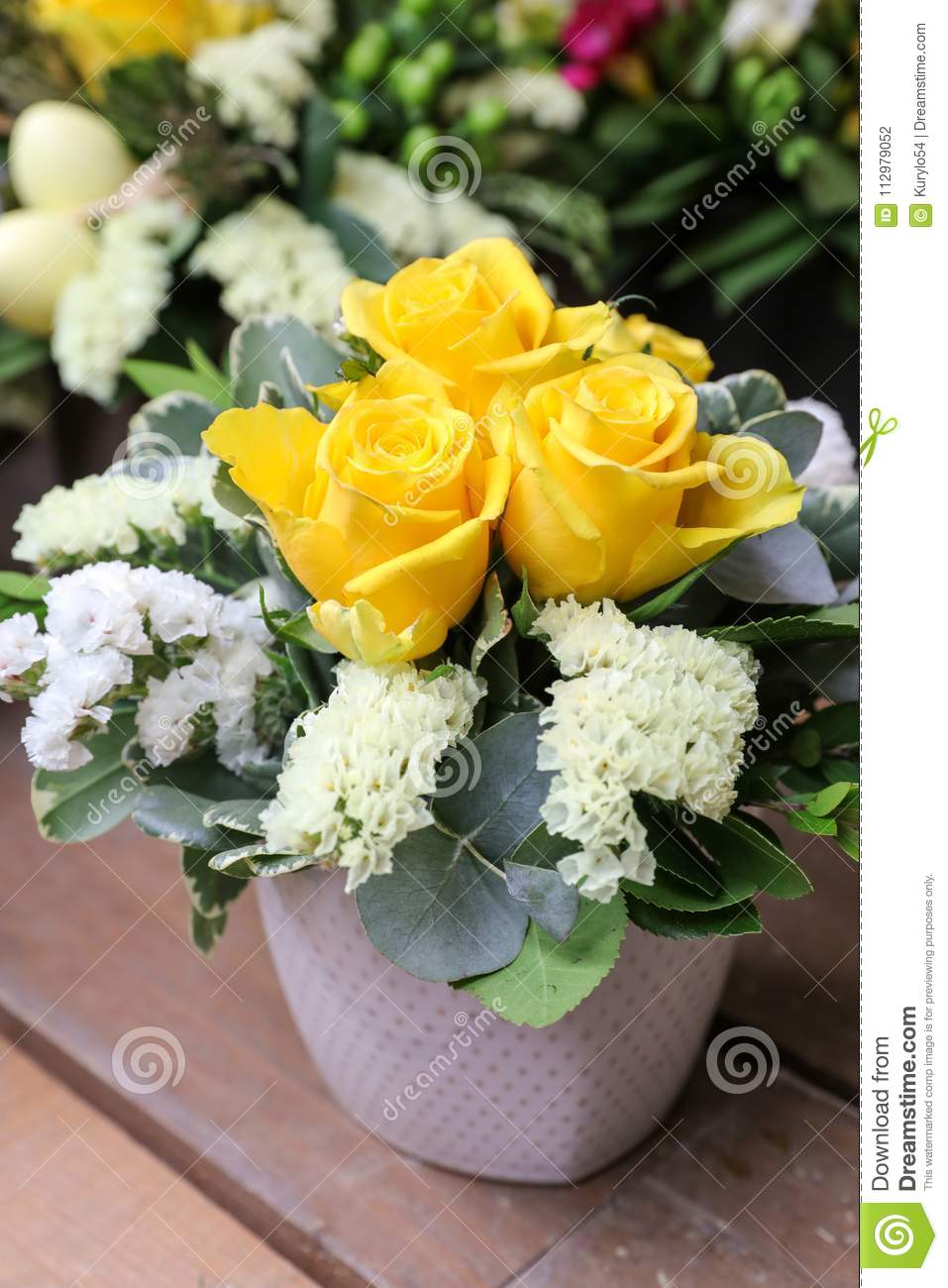 A beautiful bouquet of yellow roses and white kermek flowers in the vase.