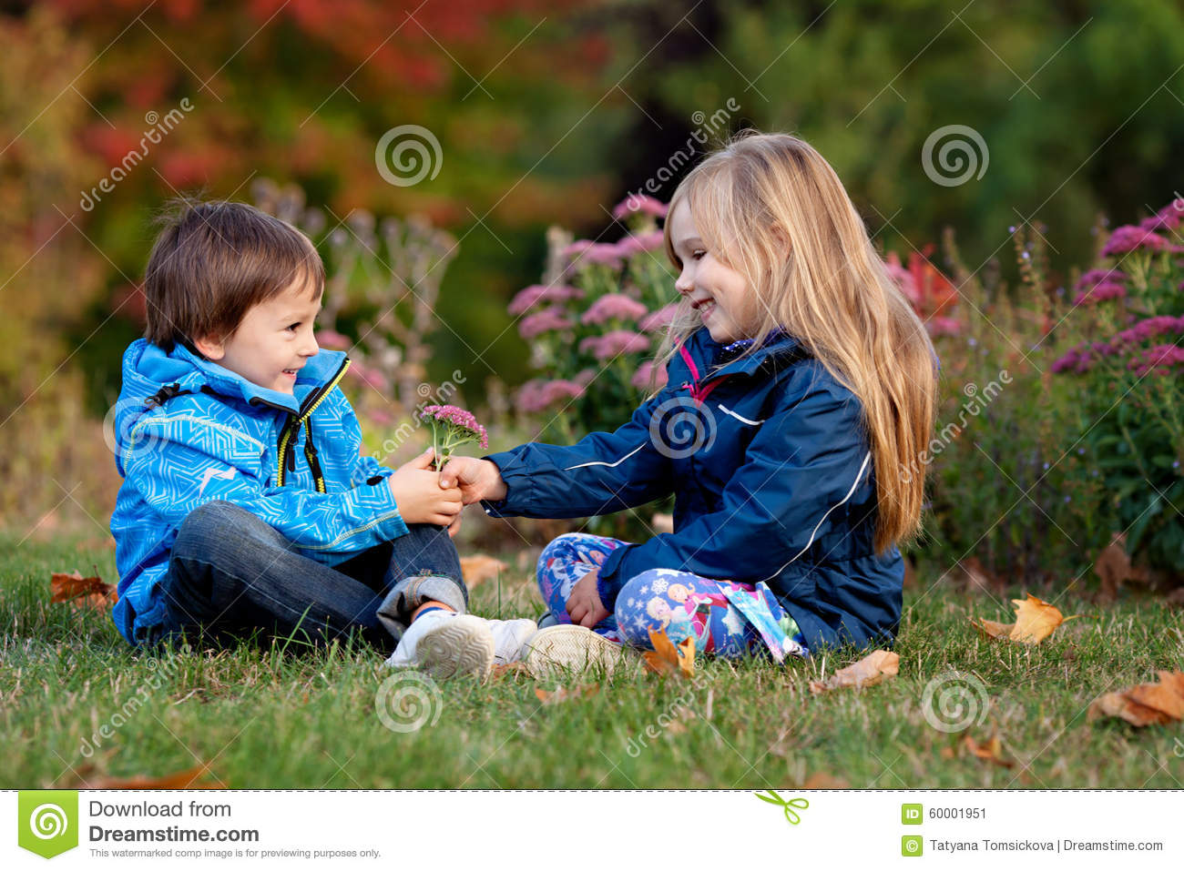 Beautiful Boy And Girl In A Park Boy Giving Flowers To The Girl
