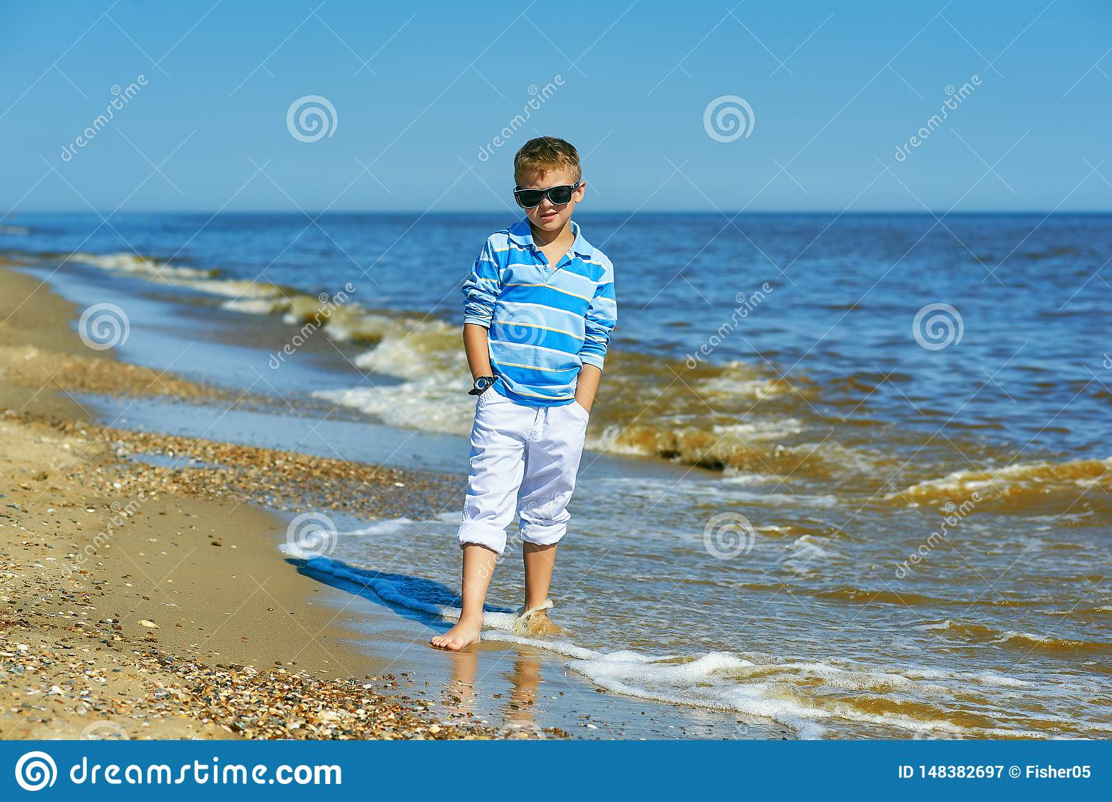 Beautiful boy posing on the seaside on a Sunny summer day .