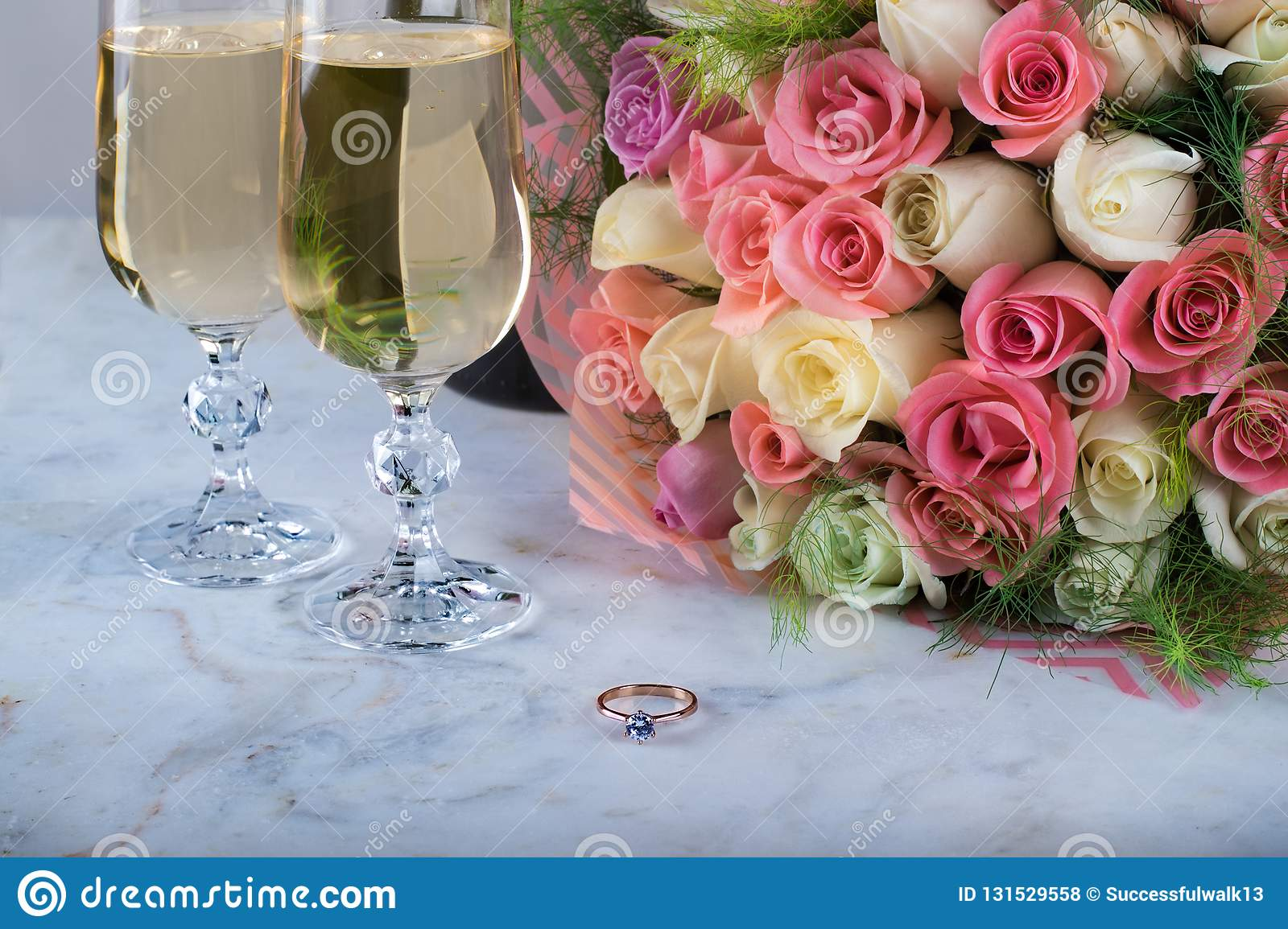 A beautiful bridal bouquet of delicate roses, a ring with a diamond, two glasses of champagne on a marble table. Festive day,