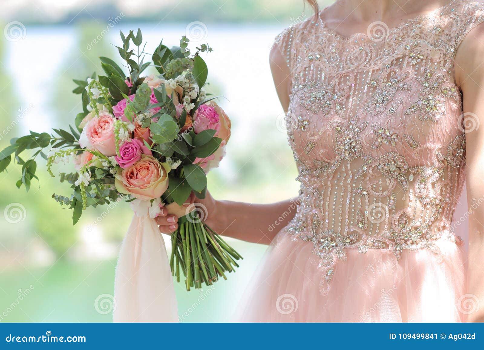Beautiful bridal bouquet in hands of the bride wedding bouquet of beautiful bridal bouquet in hands of the bride wedding bouquet of peach roses by david austin single head pink rose aqua eucalyptus ruscus gypsophila izmirmasajfo