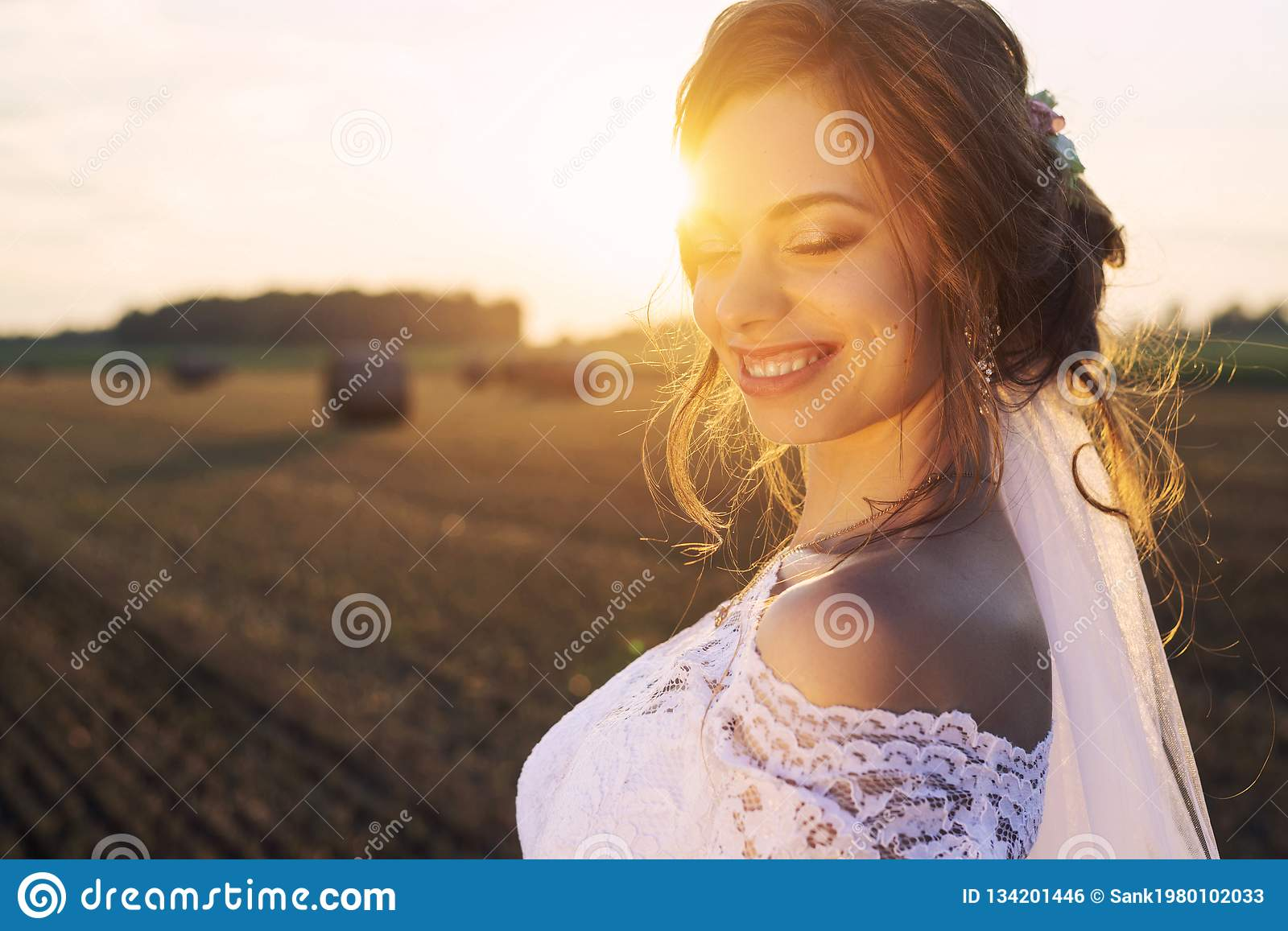 Beautiful bride in a lace dress is smiling on the background of nature