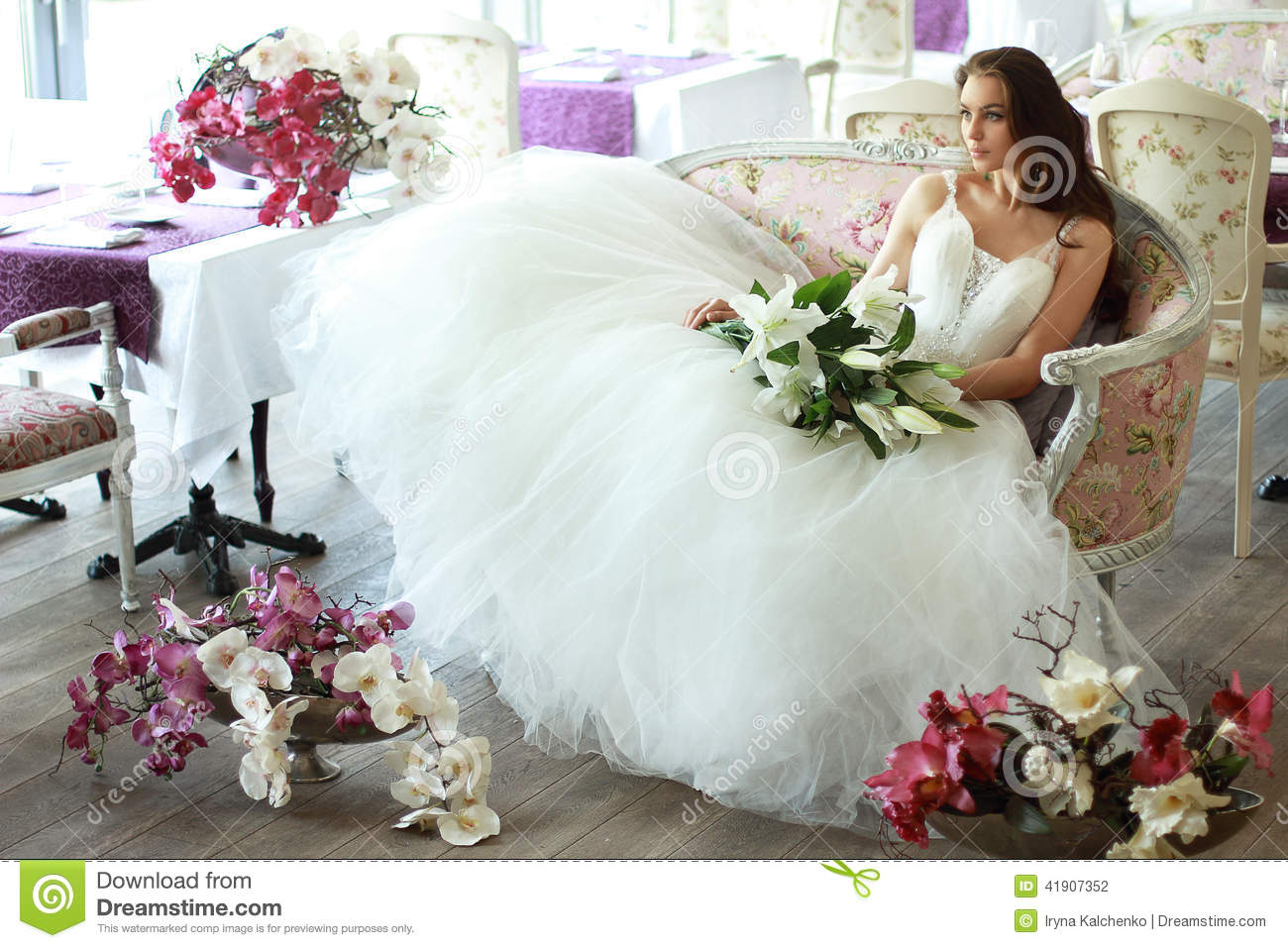 Download Beautiful Bride In A Magnificent White Wedding Dress Of Tulle With A Corset Sitting On The Sofa With Bouquet Lily And Orchid Stock Photo - Image of flowers, chiffon: 41907352