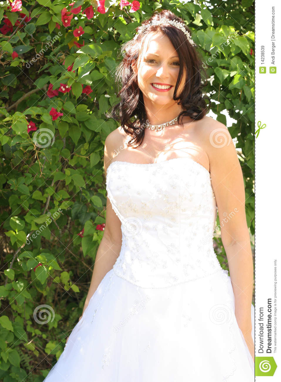 Beautiful bride outside in front of flowers