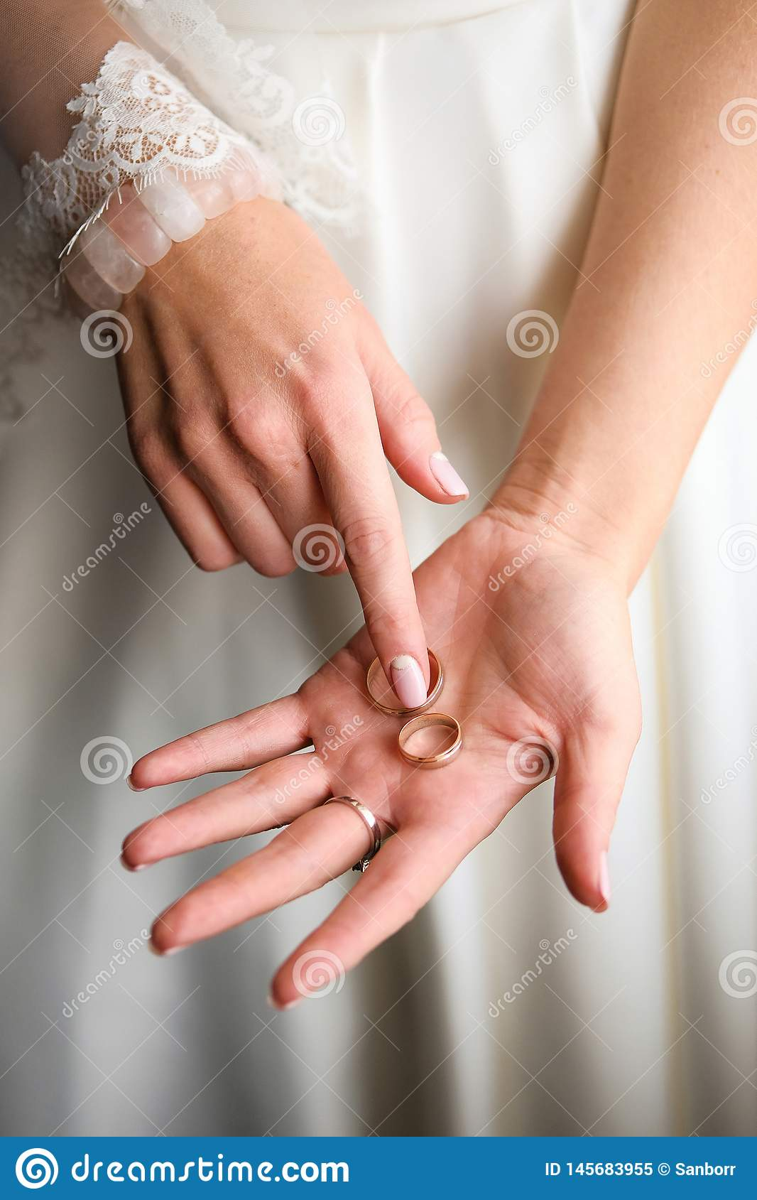 Beautiful bride in a wedding dress holding on the palm of the ring, close-up
