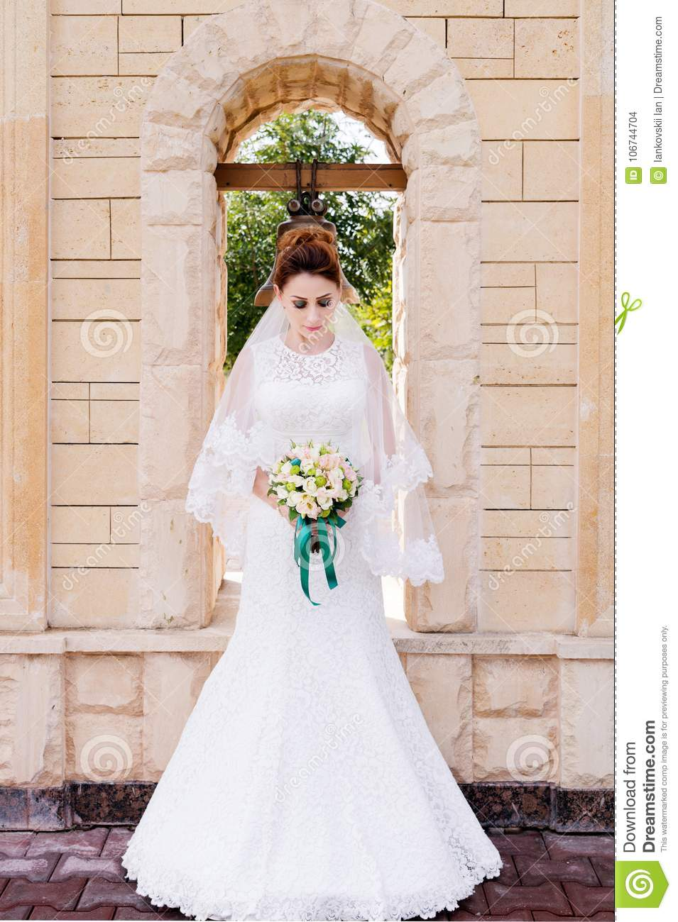 A Beautiful Bride In Wedding Dress And Bouquet Her Hands Stands Outdoors Against Stone Arch With Bell The Concept Of Happiness: Beautiful Stone Wedding Dress At Websimilar.org