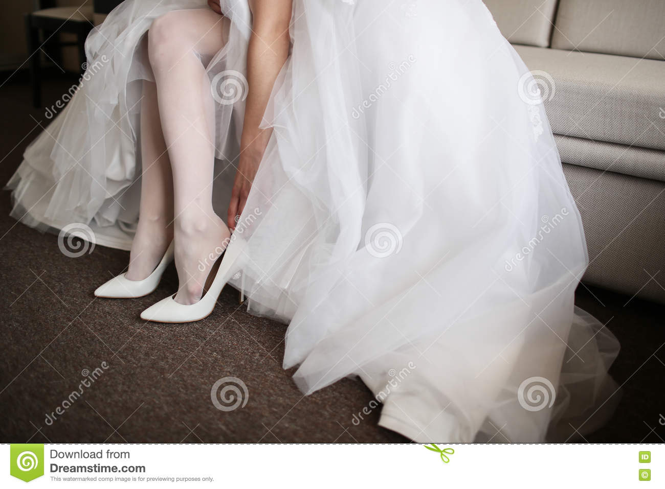 5dcb69d165f6 Beautiful bride in white wedding dress is holding shoes in her hands. .  Close-up woman s arms.