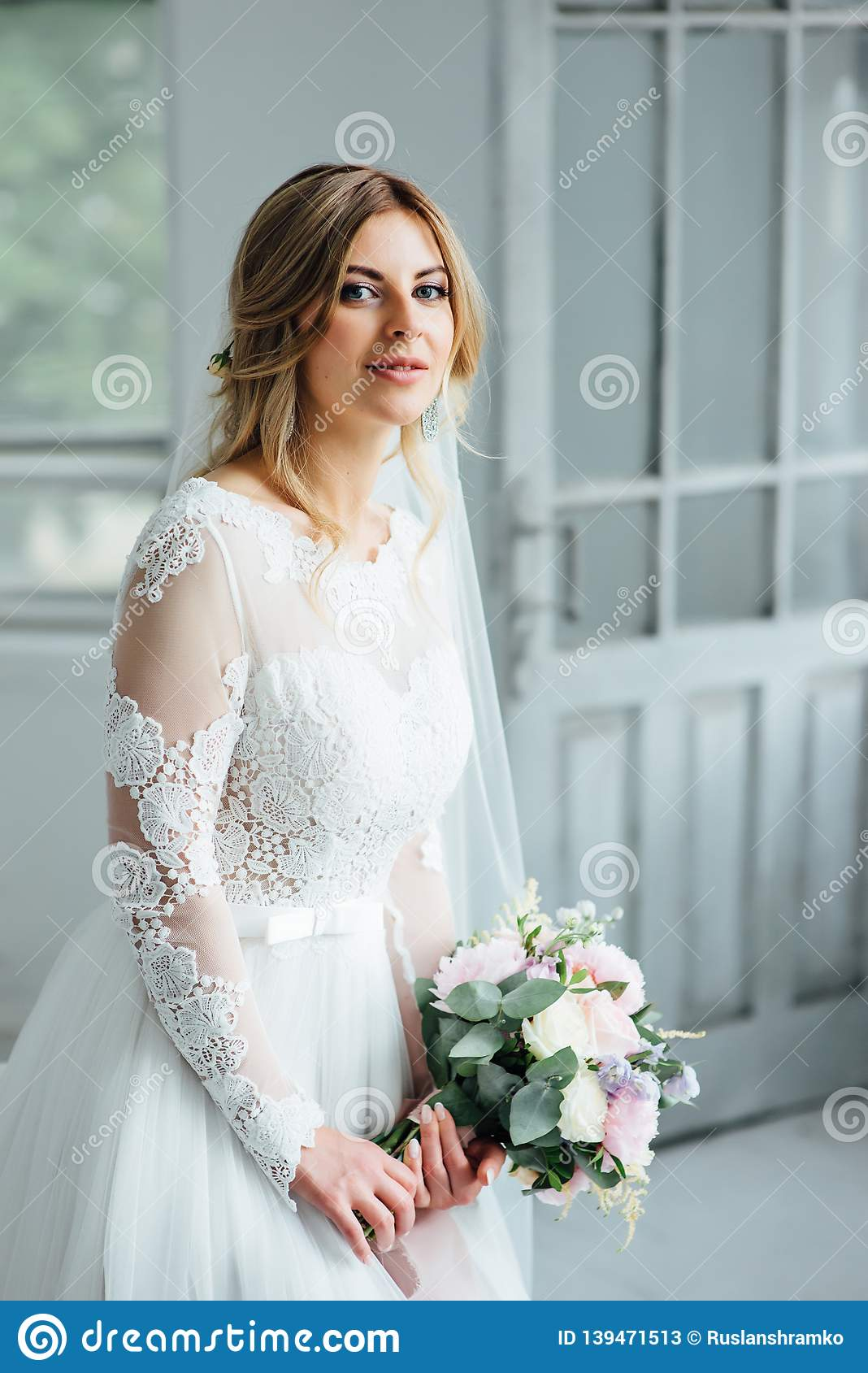 Beautiful Bride In White Wedding Dress With A Wedding Bouquet