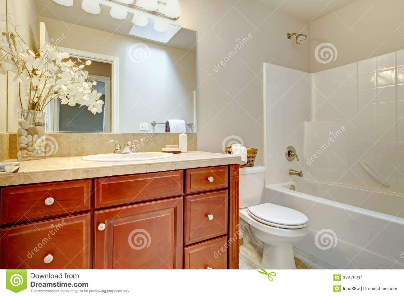 Beautiful bright bathroom with cherry wood cabinets. Beautiful Bright Bathroom With Cherry Wood Cabinets Stock Image