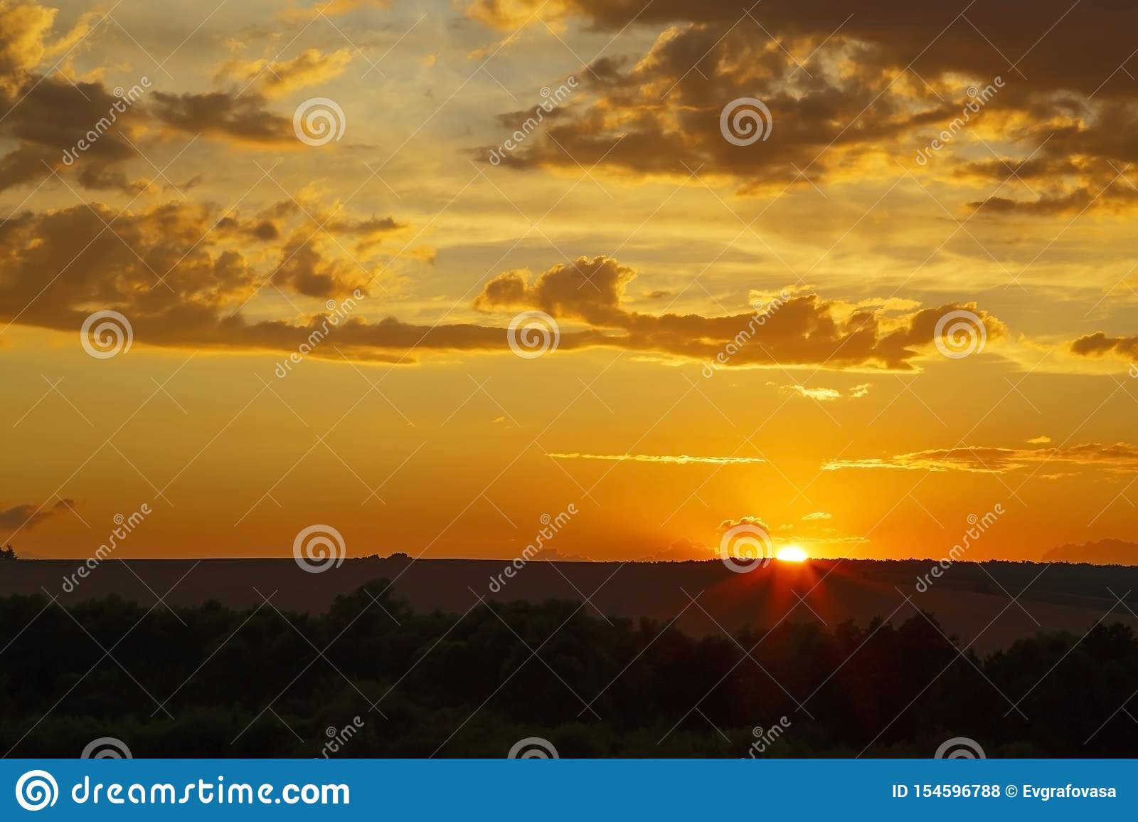Beautiful bright majestic dramatic evening sky at sunset orange color with rays. The sun shines over the horizon against the