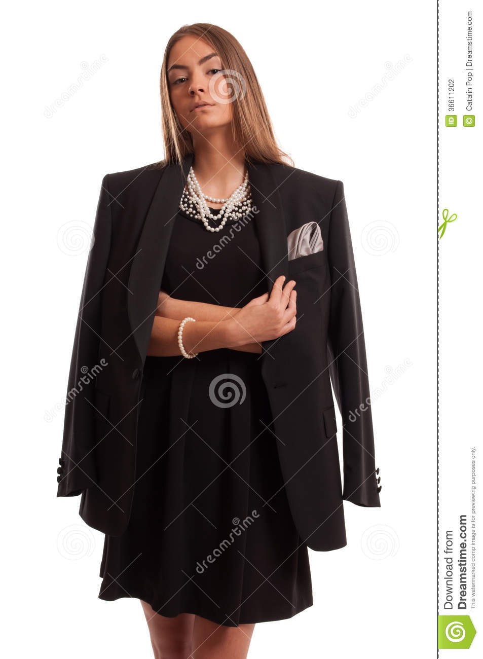 bfbcb416531 Beautiful brown haired young woman having a confident attitude wearing a black  dress and jacket with pearls around her neck