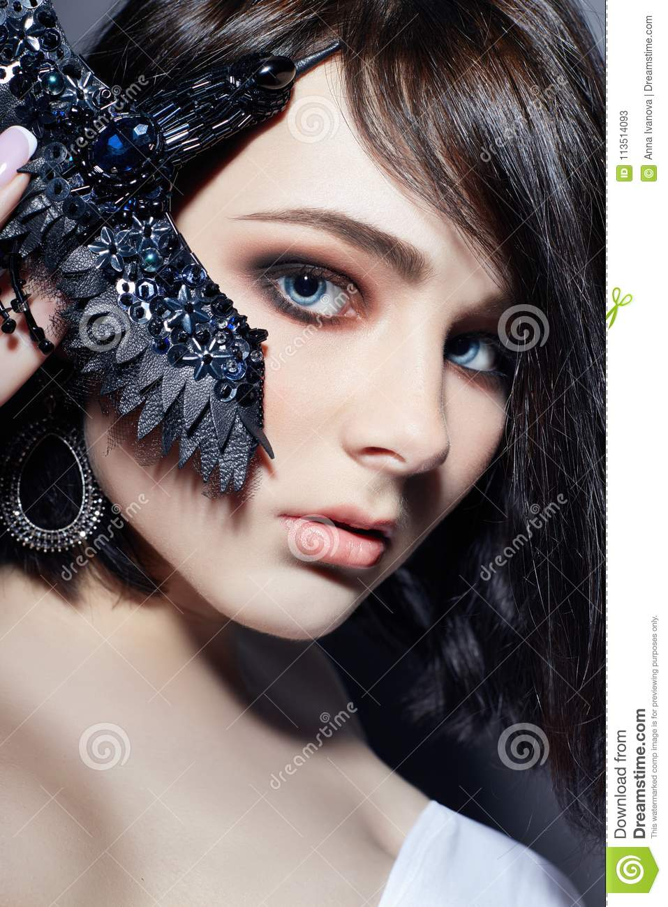 Beautiful Brunette Girl With Big Blue Eyes Holding A Black Brooch