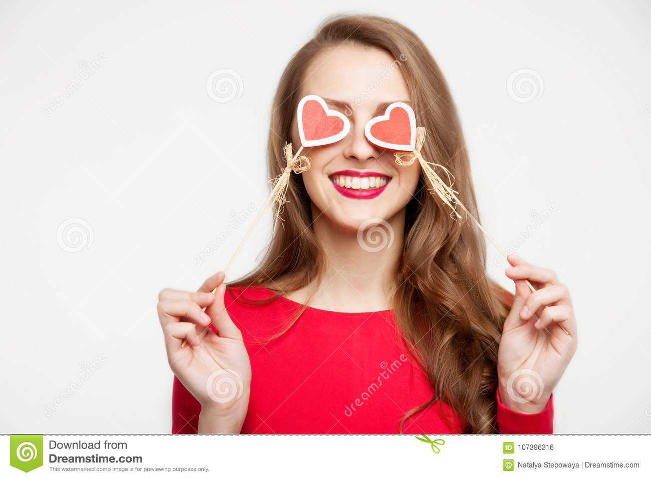 Beautiful brunette girl closed her eyes with two hearts of souvenirs. Valentine`s day concept. On white background. Place for tex