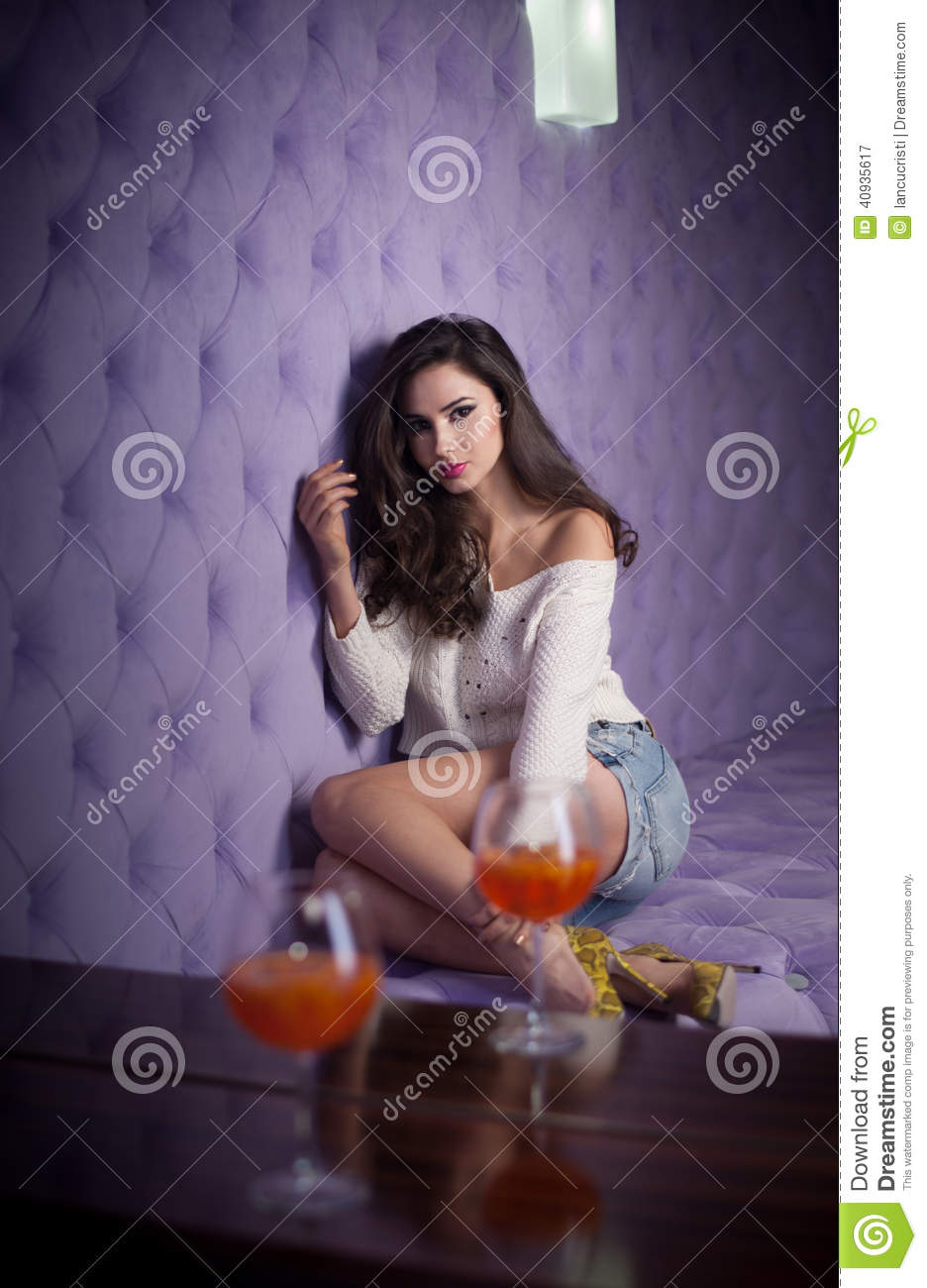 Beautiful brunette girl in denim shorts and white blouse posing on lilac textured background with two drink glasses foreground