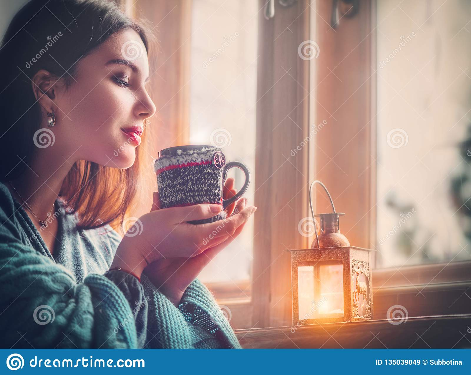 Beautiful brunette girl drinking coffee at home, looking out the window. Beauty model woman with cup of hot tea