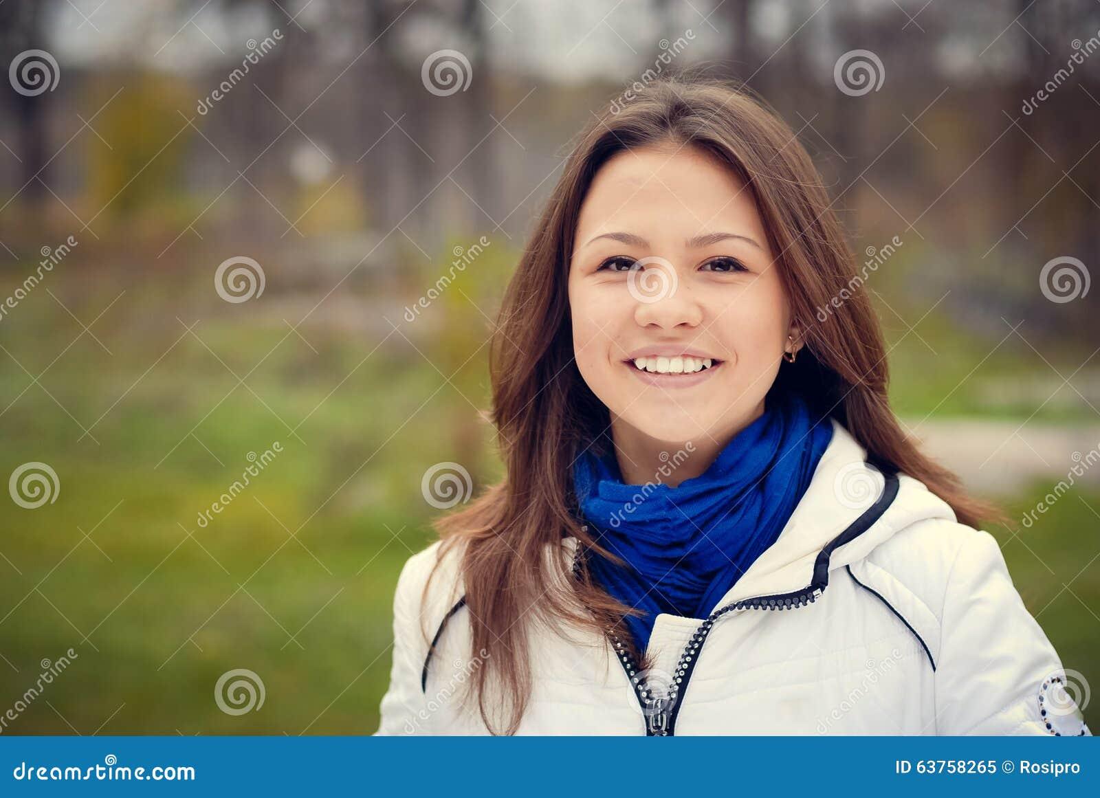 Beautiful brunette girl in white jacket smiling