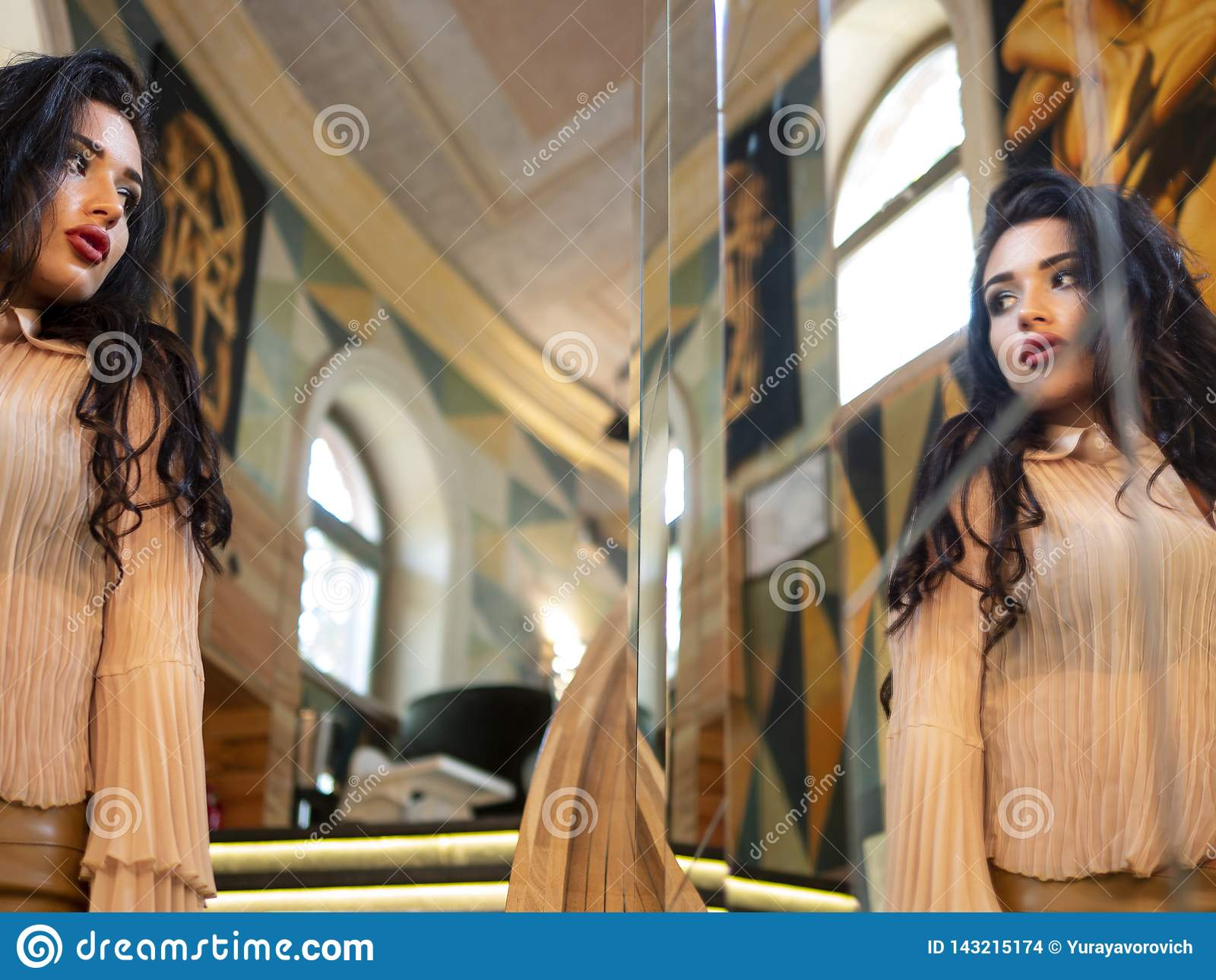 Beautiful brunette-haired model girl looks in a large mirror. fashion model posing
