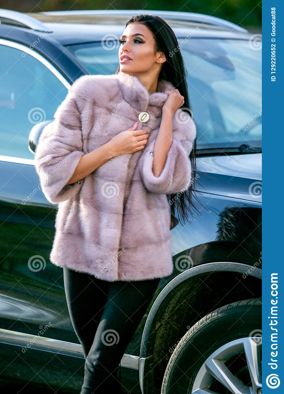 A beautiful brunette in a light-colored fur coat and black trousers is standing near a car on an autumn sunny day, sexually lookin