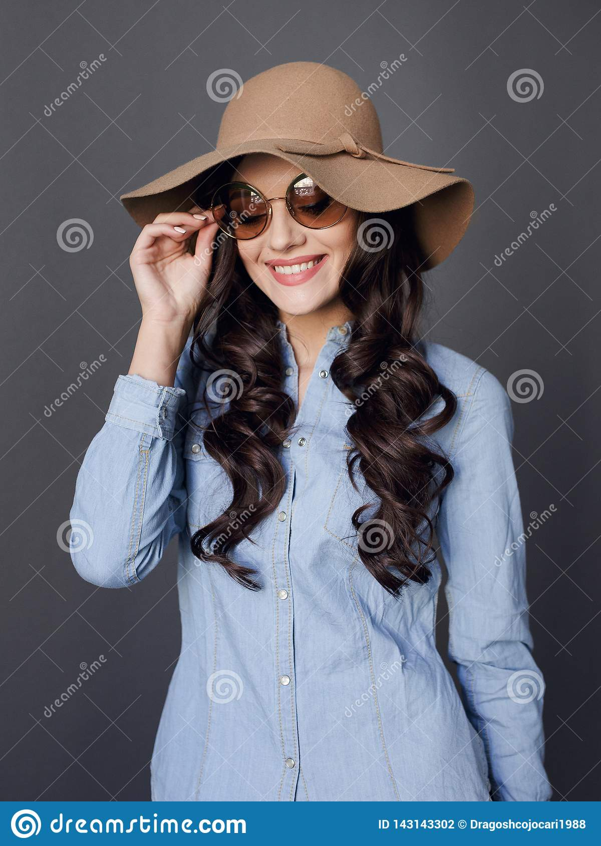 Curly haired happy brunette model, elegant dressed in hat and round sunglasses,  on a grey background.