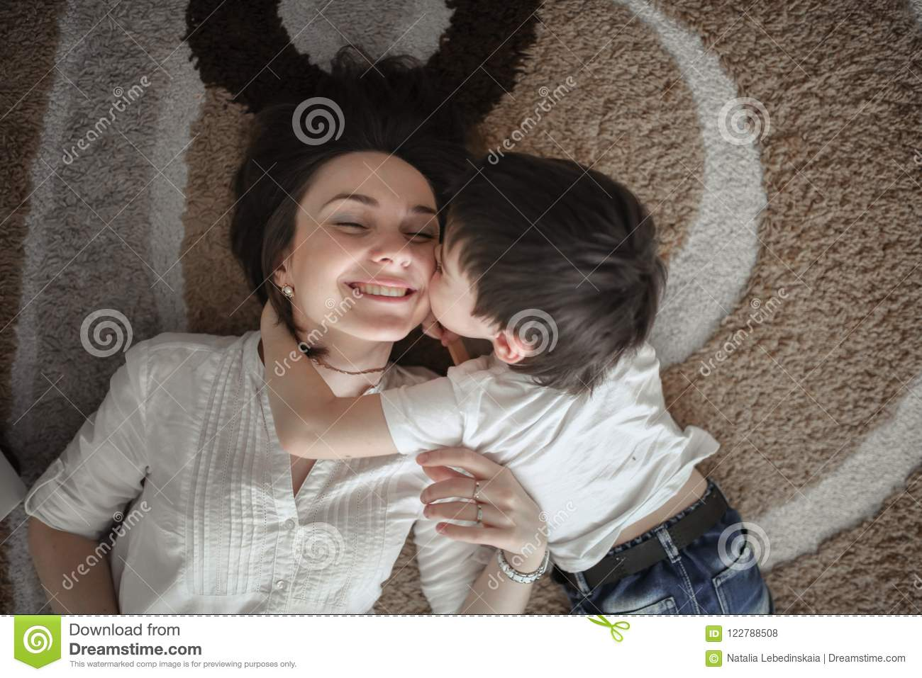 Beautiful Brunette Mom Kisses And Hugs With Her Son On The Floor In A Home Like Normal Real Interior Brown Toning Soft Focus