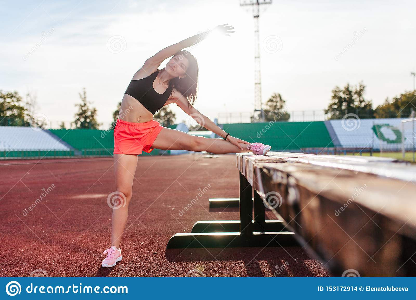 Beautiful brunette runner woman doing stretching leaning her leg on barrier for running stretching before workout - outdoor shot.