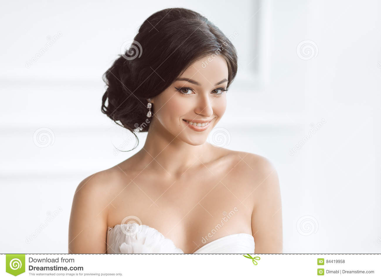 Beautiful brunette woman as bride with pink wedding bouquet on white
