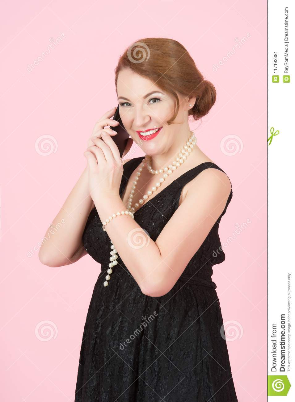 Beautiful brunette woman speak over smart phone. Cheerful woman holds telephone. Woman in black dress on pink background