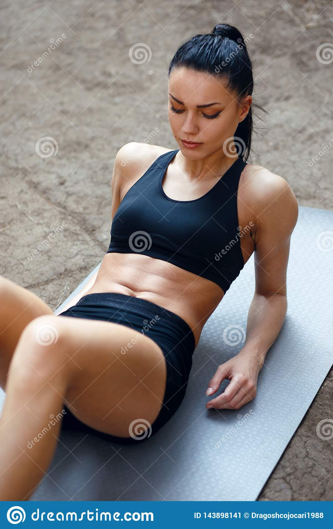 Beautiful brunette woman in sportwear Workout outside, doing press exercises. Vertical view