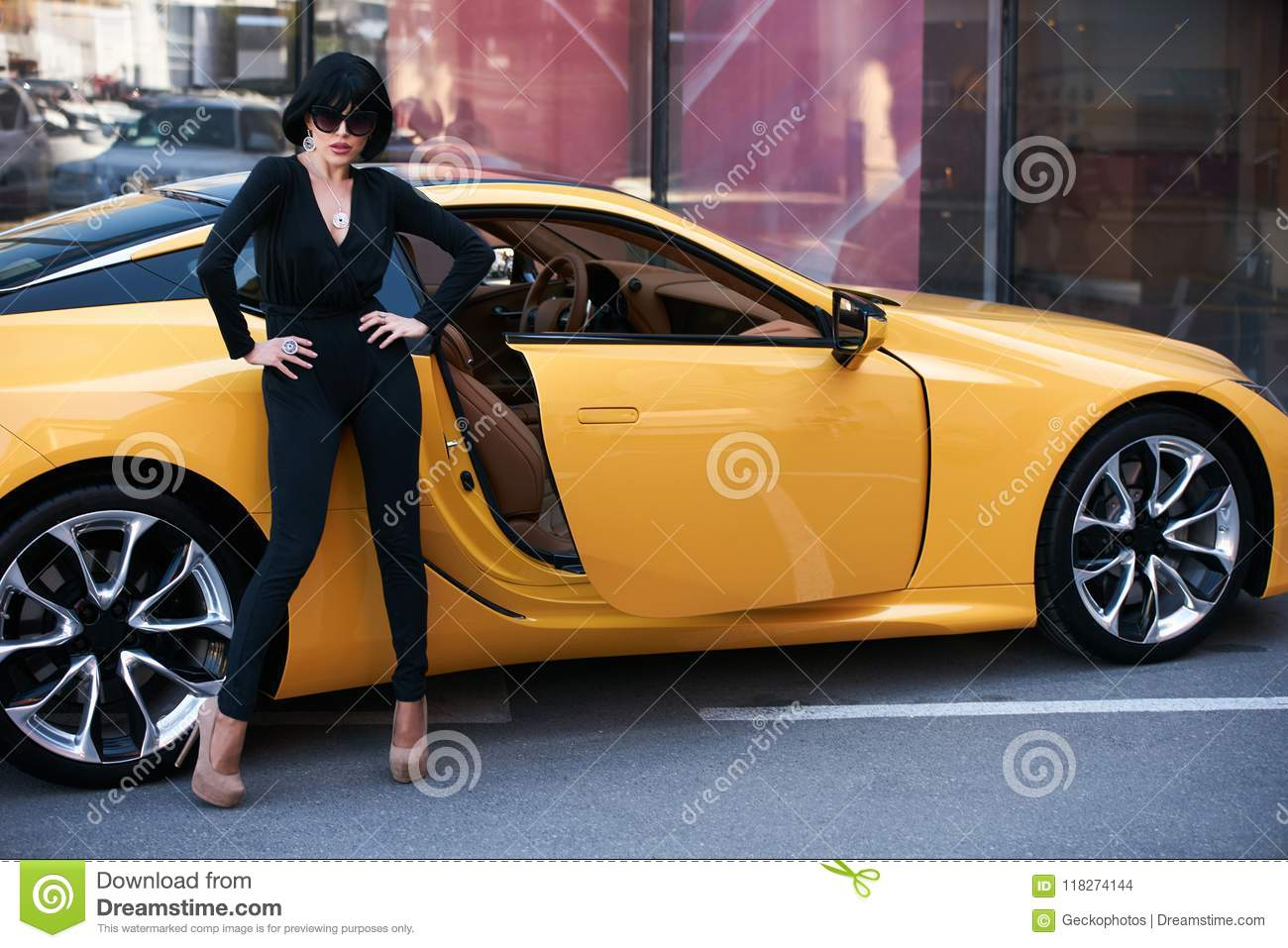 Beautiful brunette woman with yellow sport car. Young woman with dark hair  in black bodysuit and sunglasses posing near supercar 70463b681