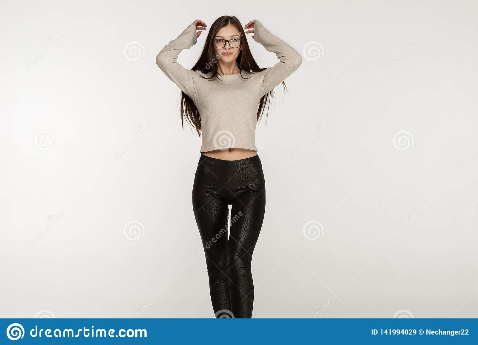 Beautiful brunette young woman in glasses and black leggings stretching arms up