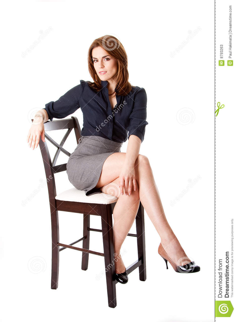 ... sitting wearing gray skirt and blue blouse with hand on leg, isolated