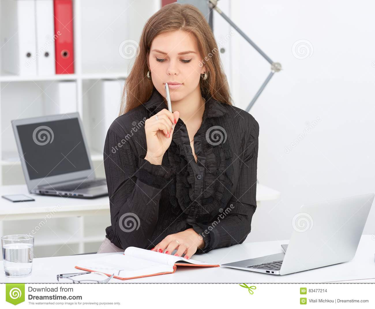 Beautiful business woman sitting at office workplace half turn looking in notebook.