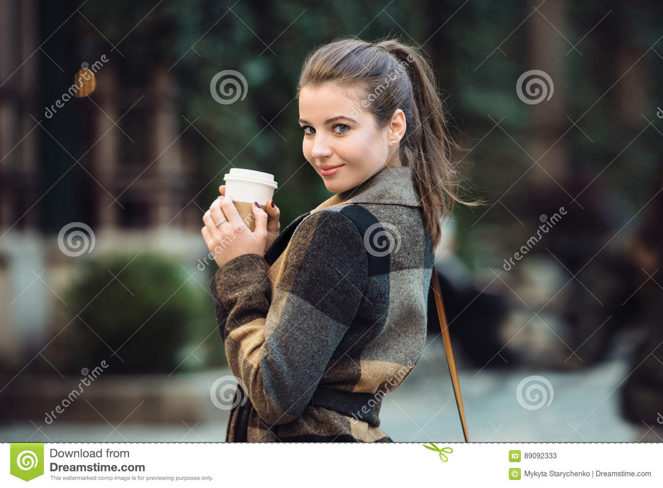 Beautiful businesswoman holding coffee cup and walking on city street to the work at spring time.