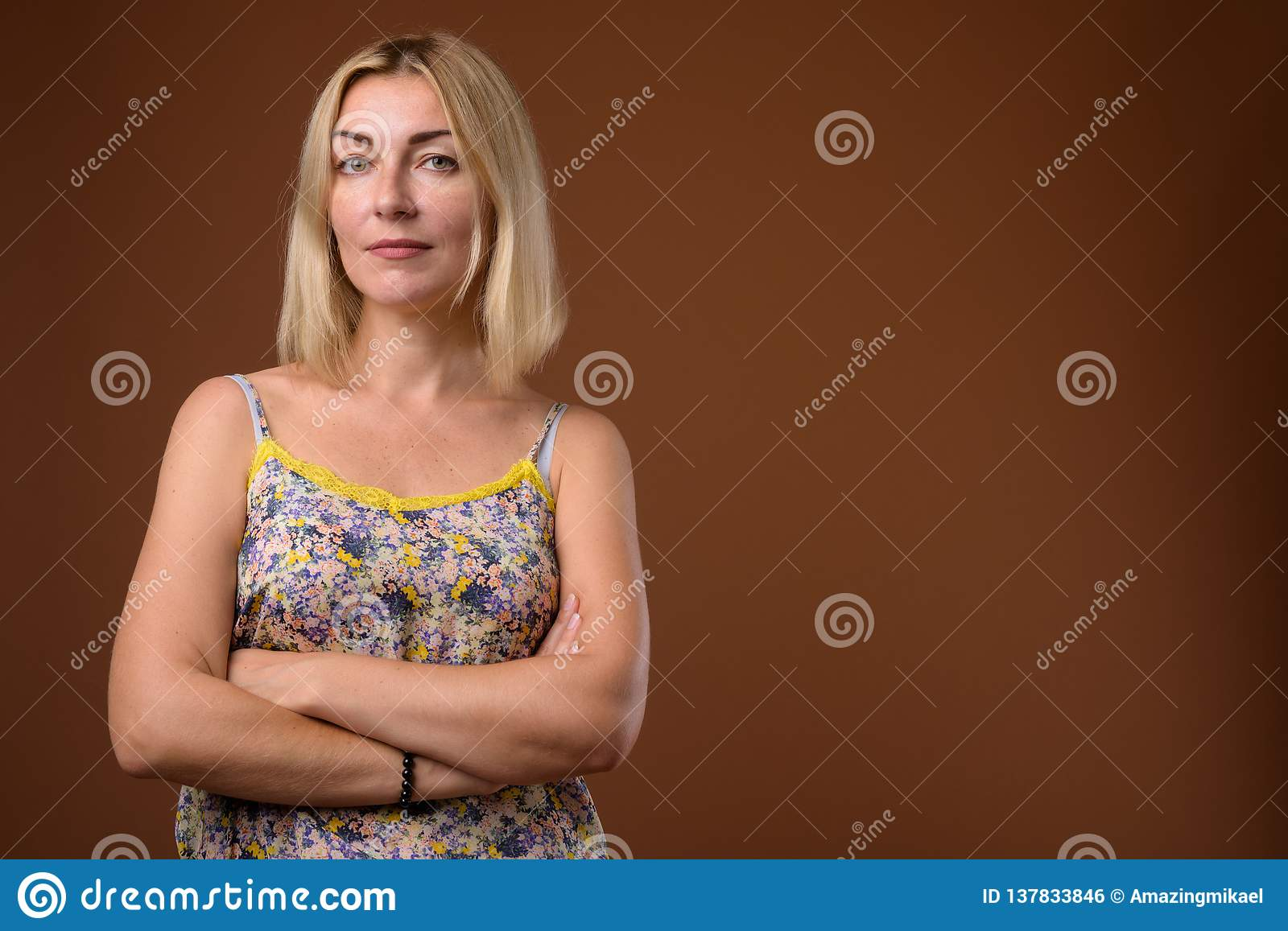 Beautiful businesswoman with short blond hair against brown back