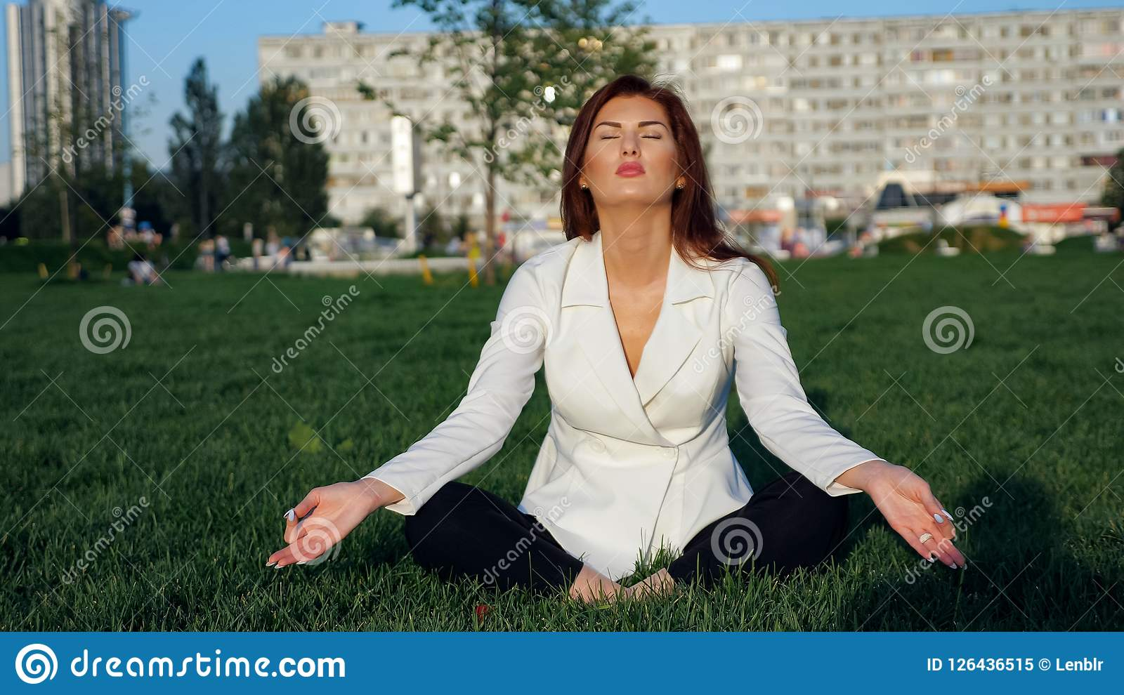 Beautiful businesswoman in white suit doing yoga for relaxation outdoor