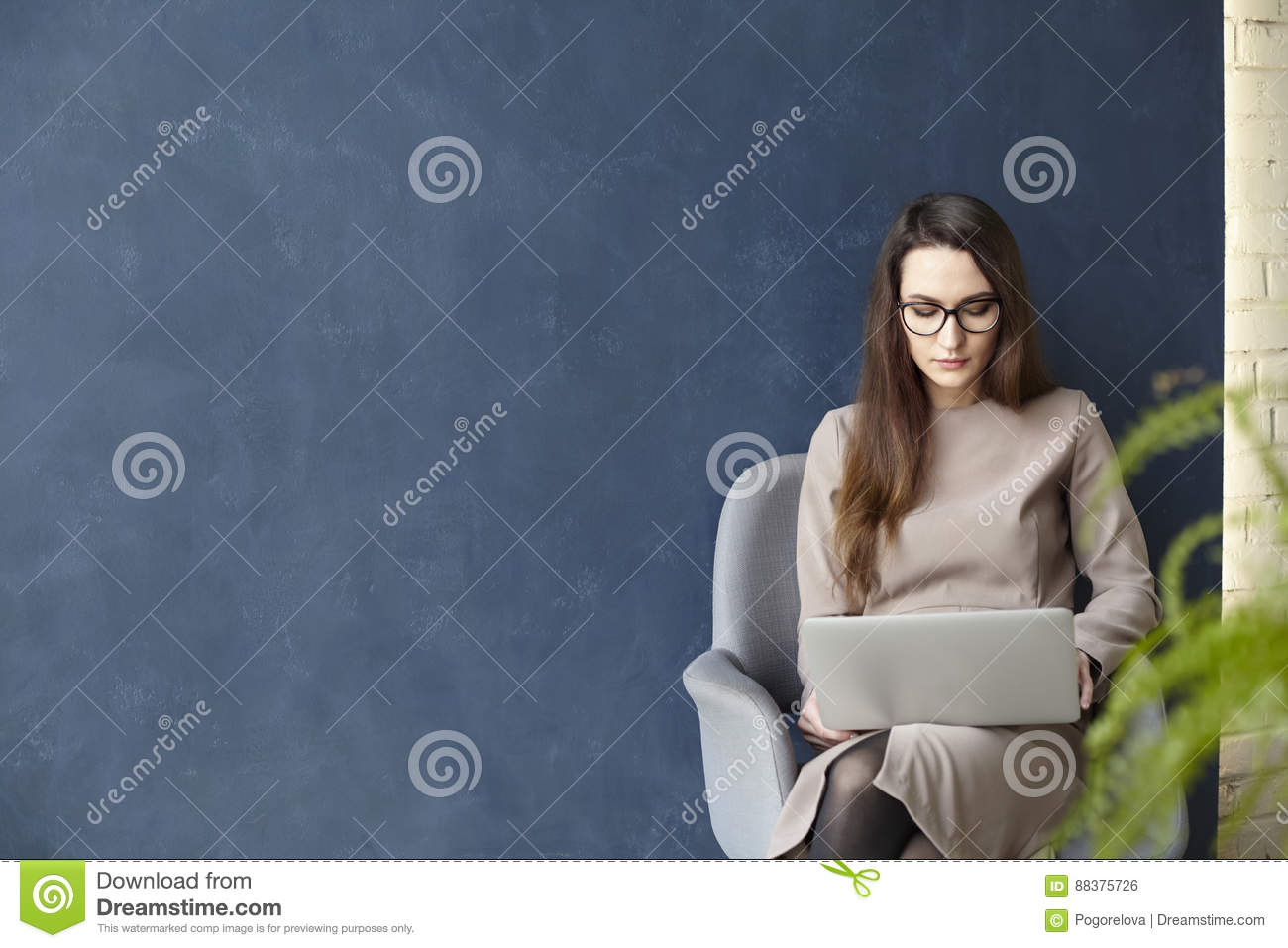 Beautiful businesswoman working on laptop while sitting in modern loft office. Dark blue wall background, day light.