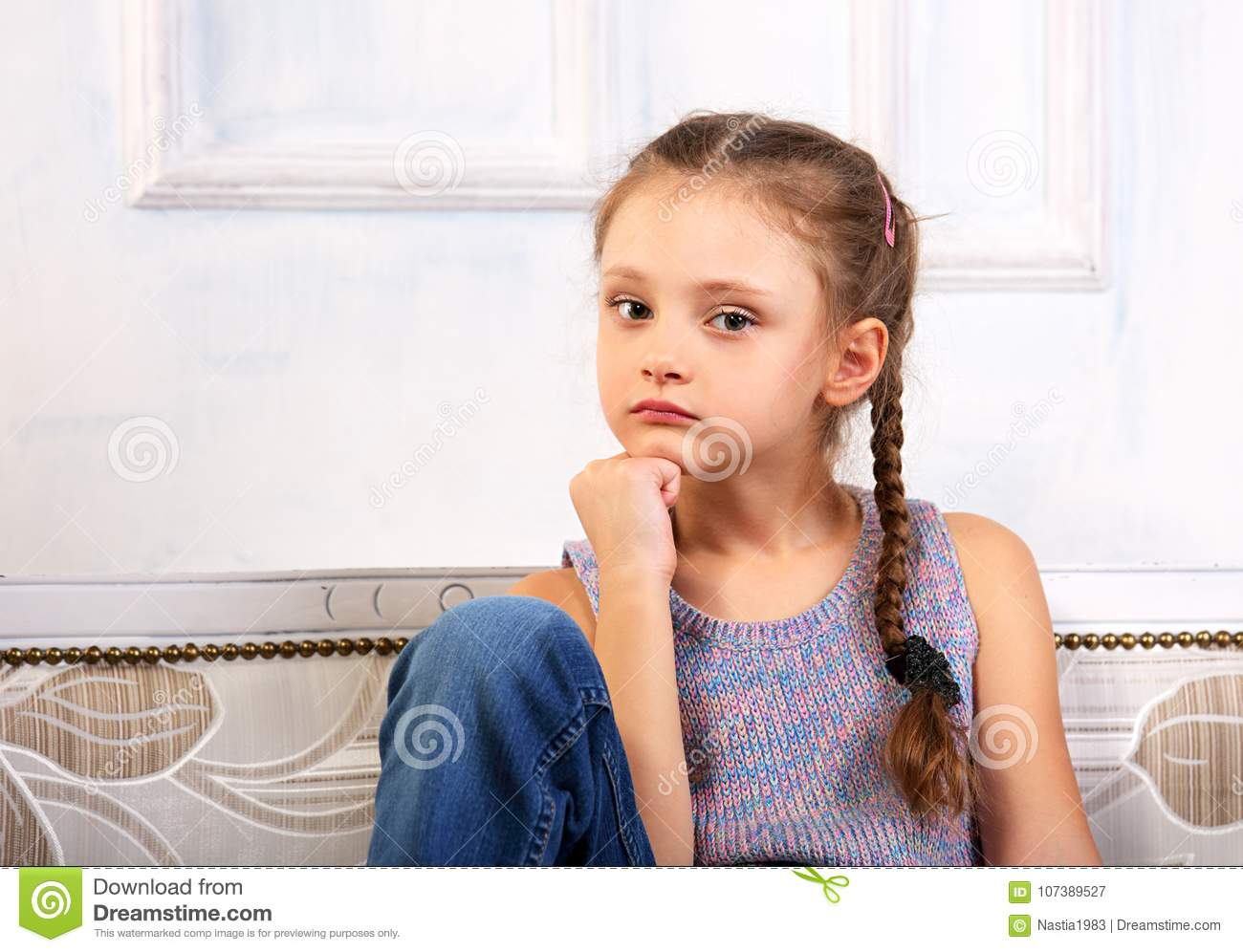 f21cc9eeb Beautiful calm thinking unhappy kid girl sitting on the bench in blue jeans  and fashion blouse looking serious. Studio portrait