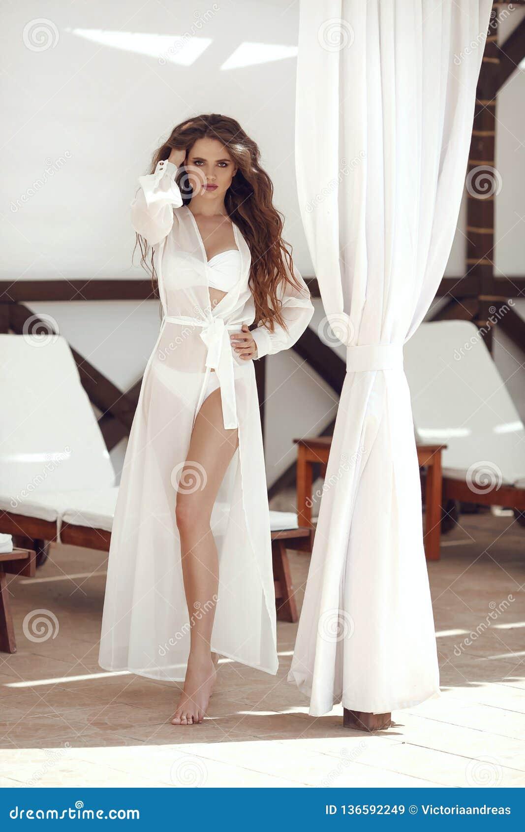 688844d030 Beautiful carefree brunette girl wearing in chiffon Wear dress by white  curtain on beach lounge resort