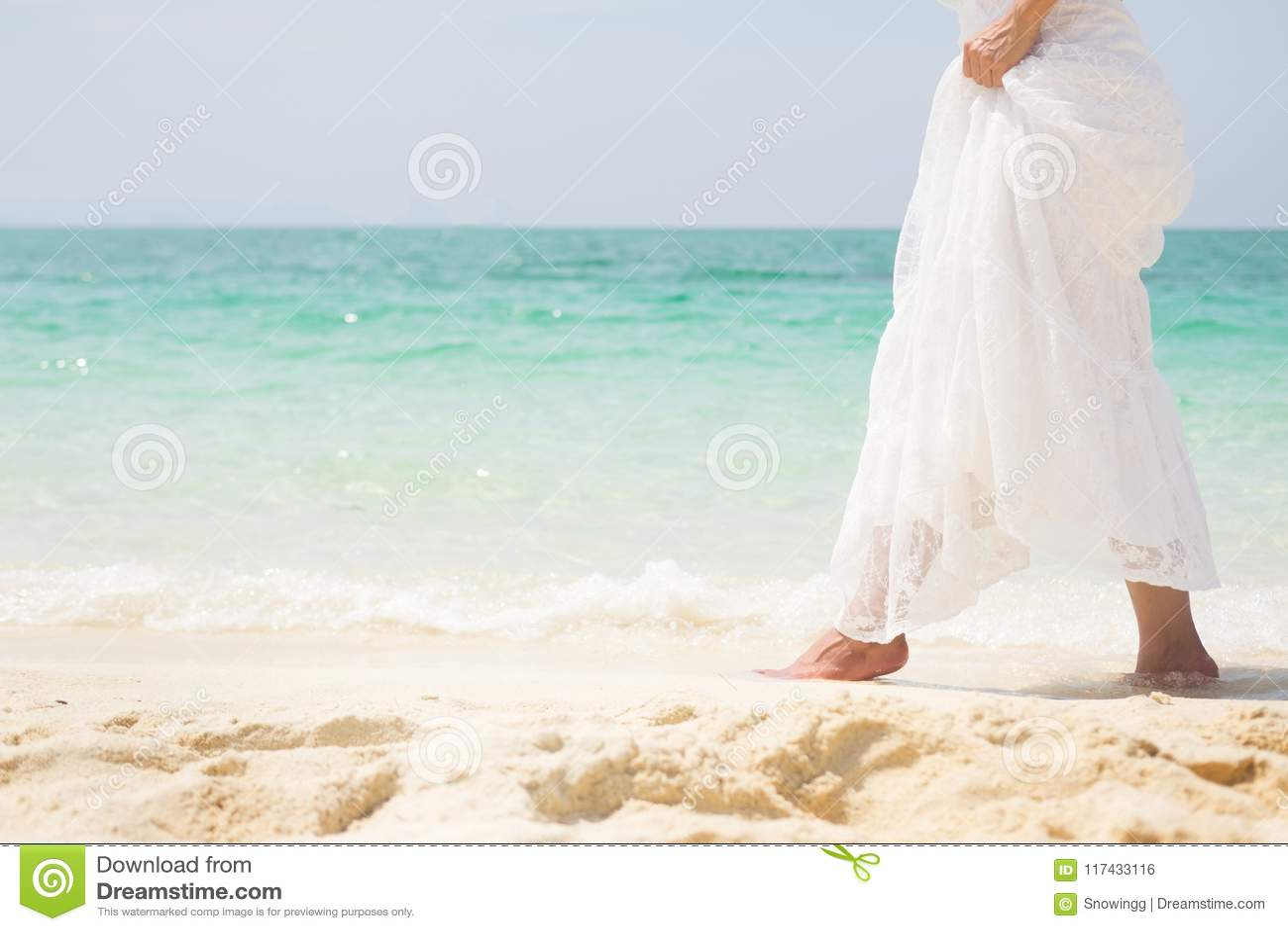 6a2739b275 A beautiful carefree Woman relaxing at the beach enjoying her sun dress  freedom wear