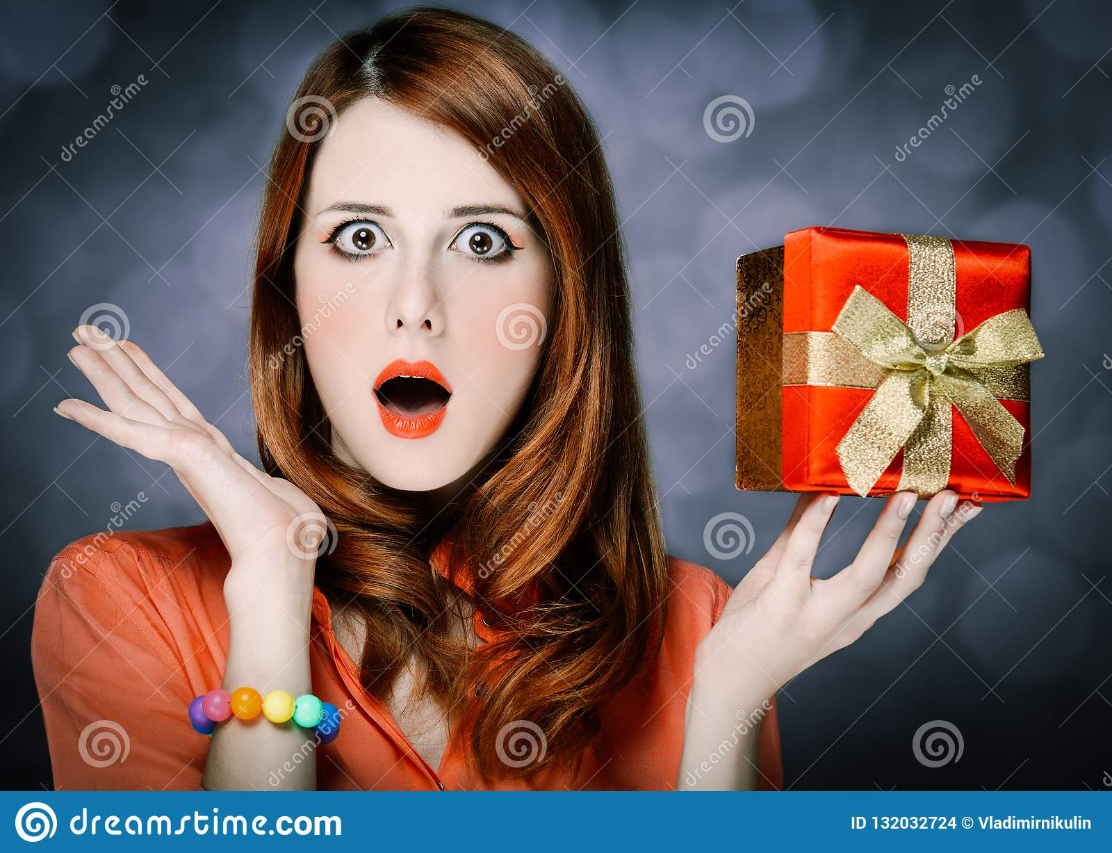 Beautiful caucasian redhead adult girl in coral shirt and gift box on gray  backgroud.
