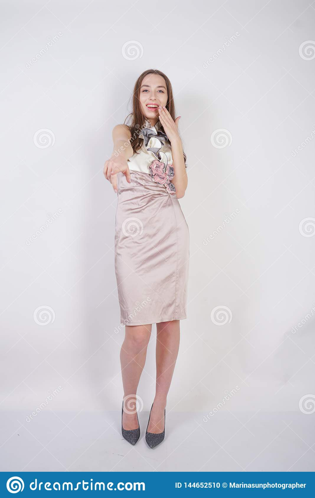 Beautiful caucasian teen girl stands in a short evening dress and mocks the interlocutor, humiliating, on a white background in th