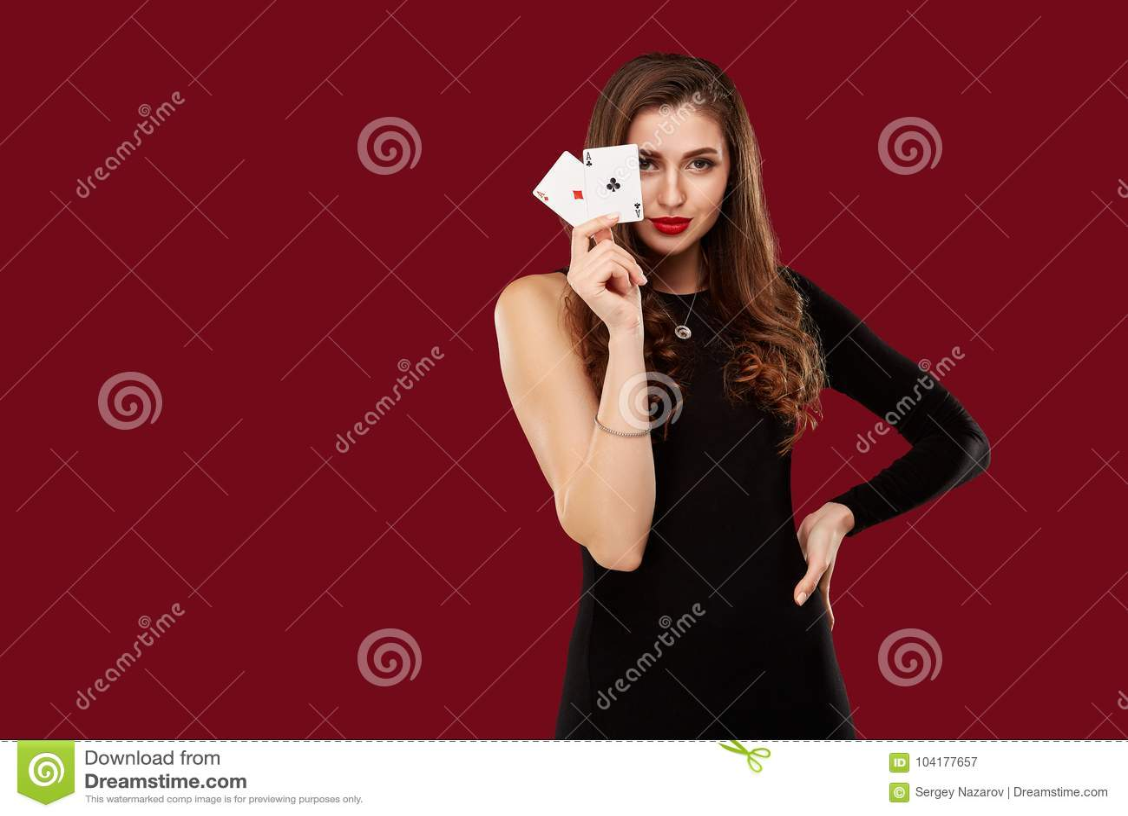Beautiful caucasian woman in black dress with poker cards gambling in casino