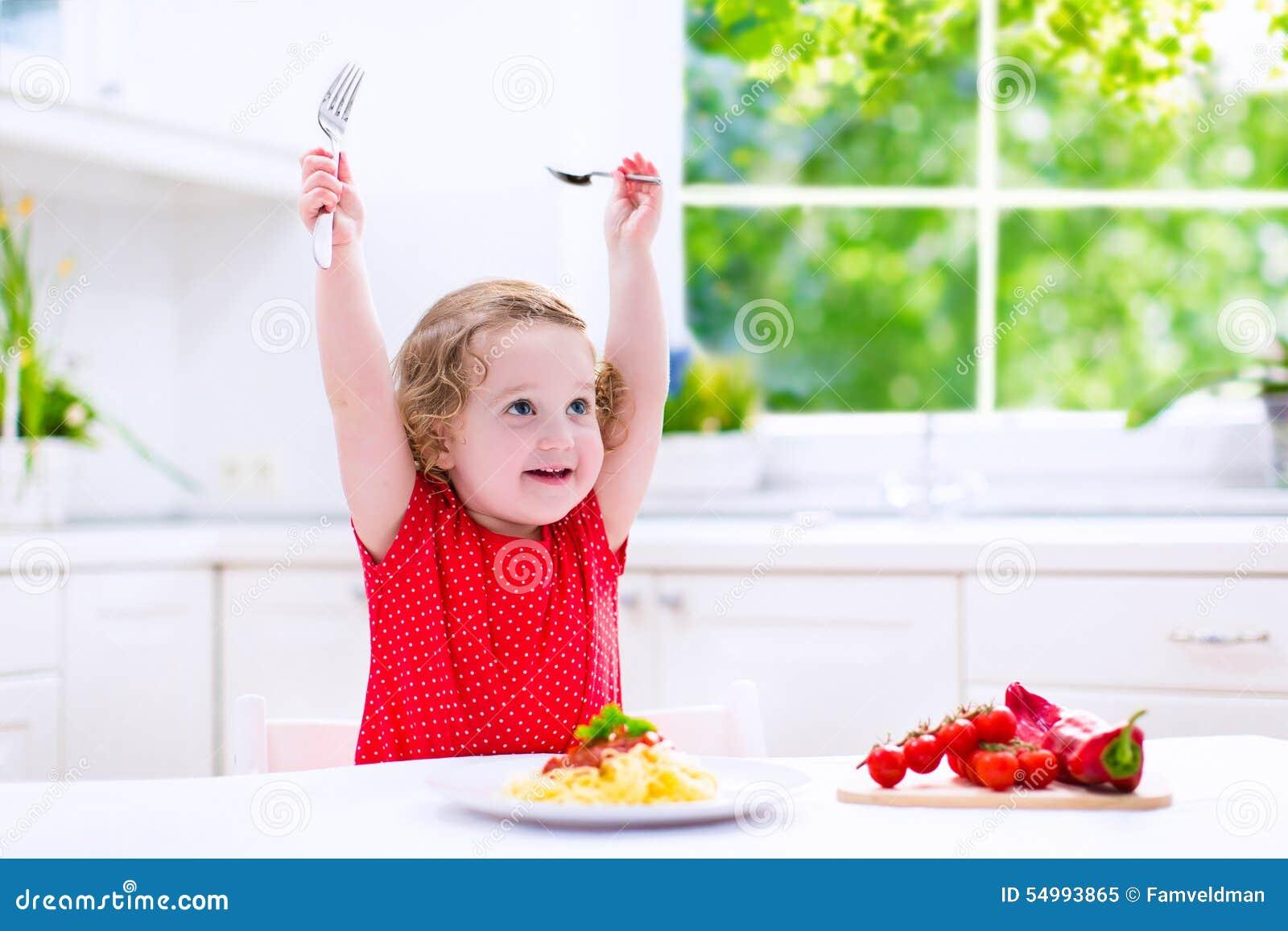 Beautiful child eating pasta
