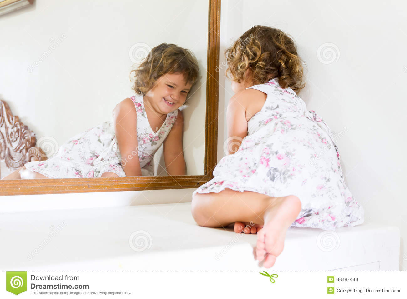 Beautiful child girl looking at herself in mirror at home for Looking for mirrors