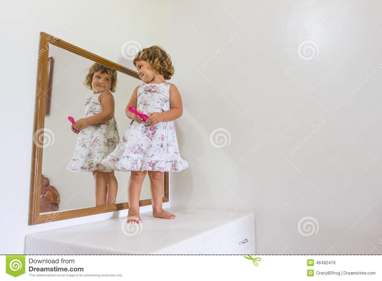 Beautiful child girl looking at herself in mirror at home stock photo