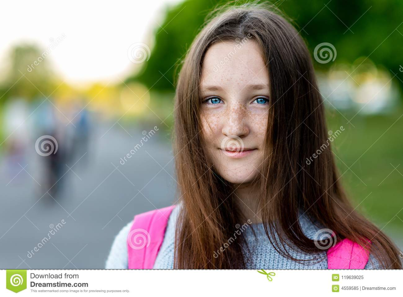 A beautiful child, teenage girl. Summer in nature. Close-up portrait. Blue eyes freckles on face. Smiles happily. Free