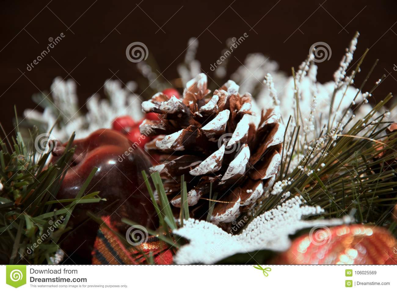 Beautiful Christmas decorations: a cone and branches of a Christmas tree under snow