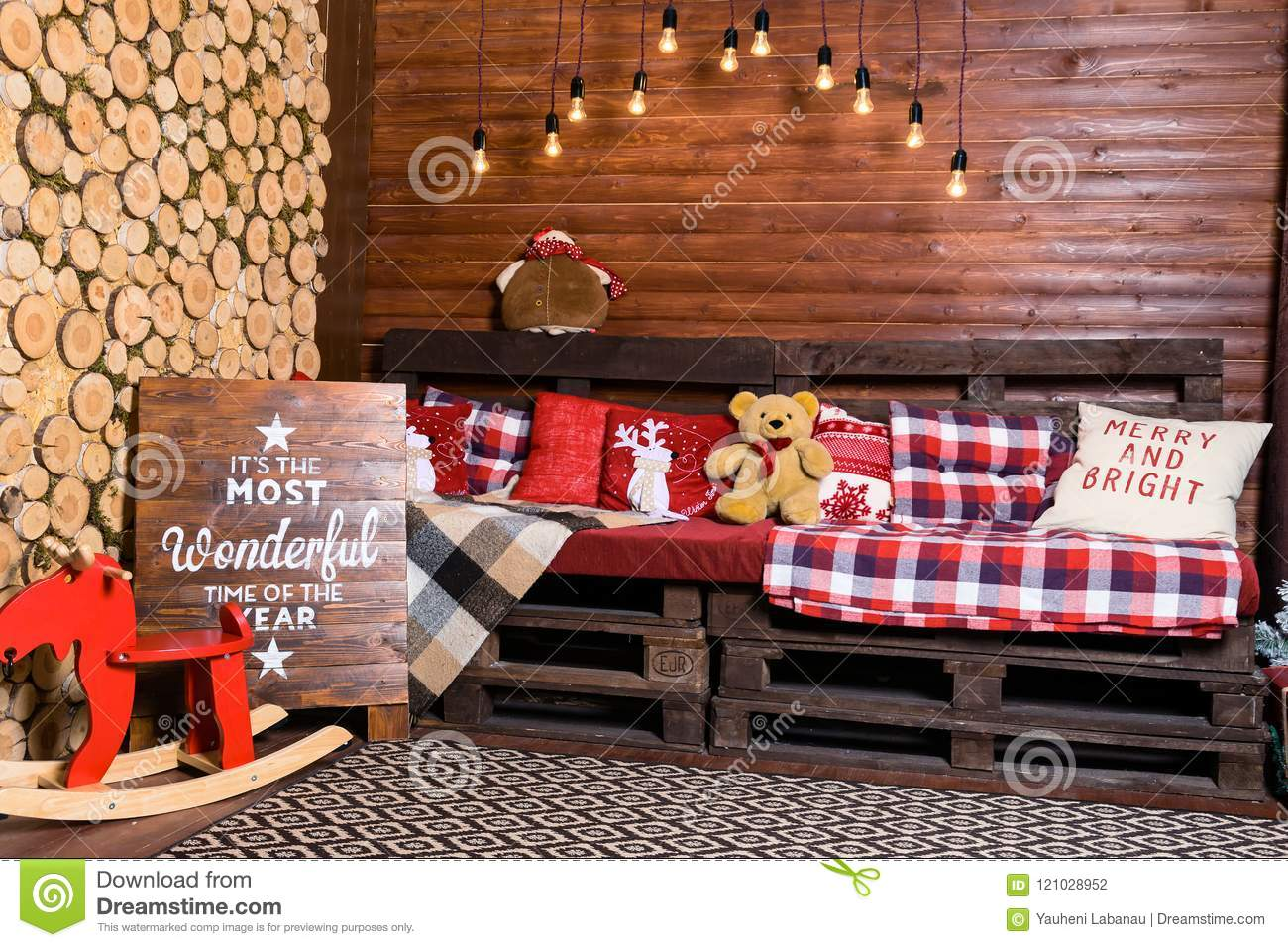 beautiful christmas interior design room decorated with wooden sofa with warm blanket lights teddy bear and wooden horse