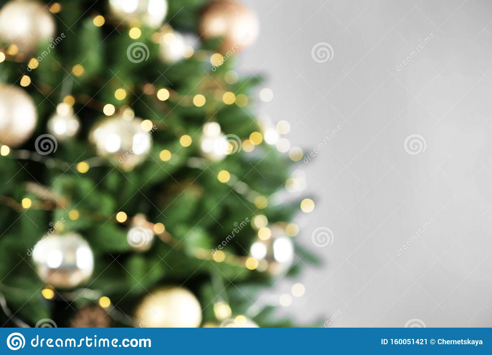 Beautiful Christmas tree with lights against grey background, blurred view